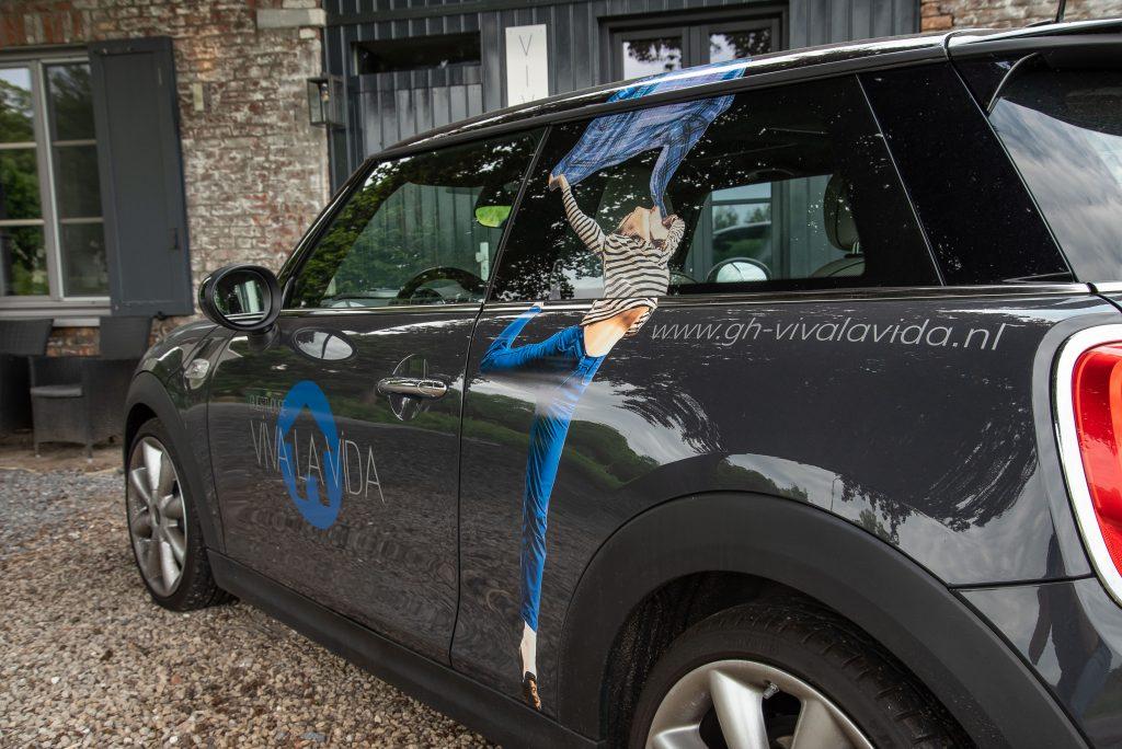 Bedrukte bedrijfsauto geparkeerd voor Guesthouse Viva La Vida Maastricht.